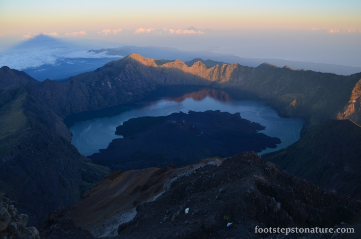 7.00am – The caldera rim and lake majestically illuminates as the sun rises. At the top left you'll notice the shadow of Mt Rinjani's peak and on the background you can also notice Mt. Agung of Bali